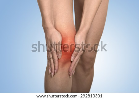 Closeup tendon knee joint problems on woman leg indicated with red spot isolated on blue background. Joint inflammation concept. - stock photo