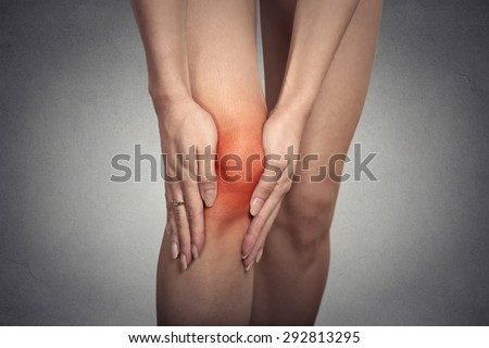 Closeup tendon knee joint problems on woman leg indicated with red spot isolated on gray background. Joint inflammation concept. - stock photo