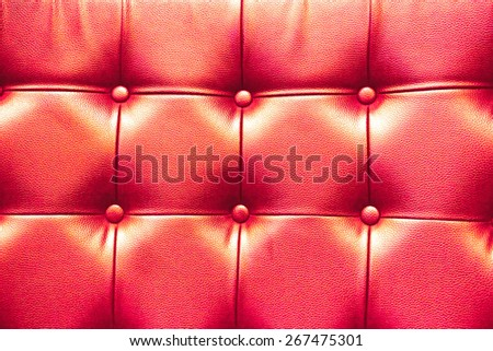Closeup texture of vintage red leather sofa with shadow and light . - stock photo