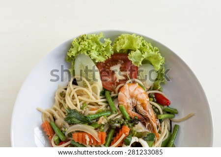 Closeup Thai style fried spaghetti with spicy seafood and vegetables with space on white wood background