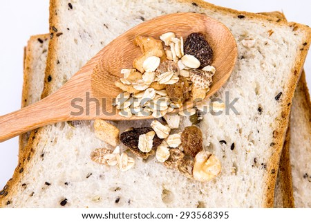 closeup the cereal and black sesame bread with whole grain cereal flakes which mixed warming cinnamon , red skin apple , golden raisins and roasted hazelnuts - stock photo