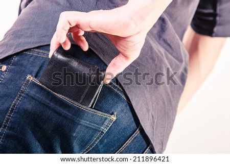 Closeup. Thief stealing wallet from back pocket of careless man. Risk of theft. Isolated on white. Studio shot. - stock photo