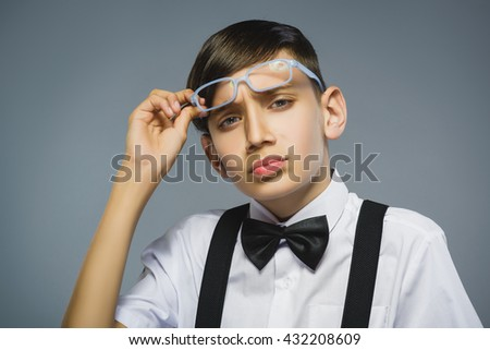 Closeup Thoughtful Young Boy with hand on glasses Against Gray Background - stock photo