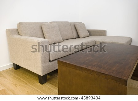 closeup to a modern sofa with massive wood coffee table