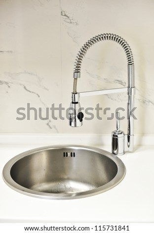 closeup to a modern stainless steel kitchen sink .designer kitchen sink with chrome water tap - stock photo