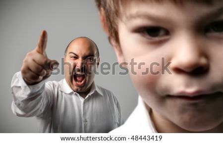 Closeup to a sad child and man shouting on the background - stock photo