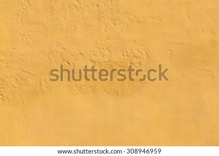 Closeup to a wall painted yellow with lumps on it. There is space for text - stock photo