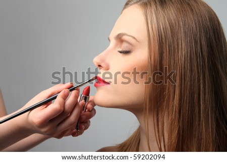 Closeup to a woman during makeup - stock photo