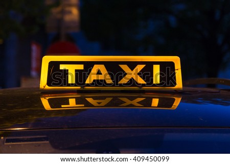 Closeup to a yellow and black taxi sign on a top of a car. Reflections can be seen on the car roof. - stock photo