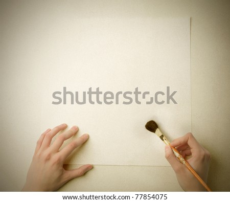Closeup to man's hands using a brush on a paper sheet - stock photo