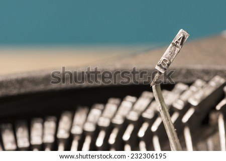 Closeup to typebars of an antique mechanical desktop typewriter with the letter A up - stock photo