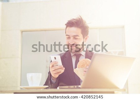 Closeup toned image of happy businessman looking at his mobile or smart phone while sitting in restaurant or cafe in front of laptop computer. - stock photo