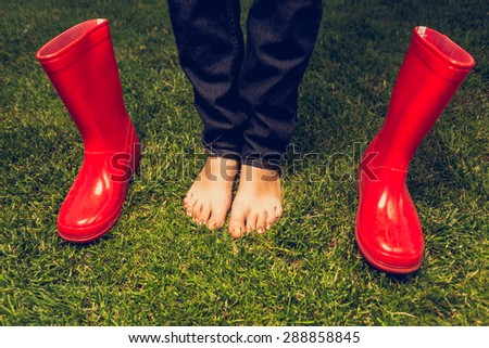 Closeup toned photo of barefoot girl posing with red gumboots on meadow