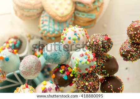 Closeup toned photo of colorful cake pops and cookies with icing - stock photo