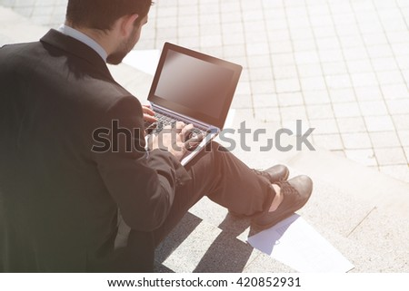 Closeup toned picture of businessman in black business suit using laptop computer in city center. Handsome man is freelancer. - stock photo
