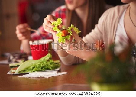 Closeup toned picture of lady eating vegetarian dishes in cafe or restaurant while sitting at wooden table. Vegetarian concept. - stock photo