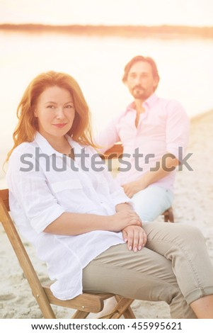 Closeup toned picture of red-haired woman happy smiling. Handsome man sitting on chair behind her. People having rest at beach near by sea.