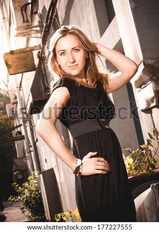 Closeup toned portrait of beautiful woman in black dress against old building