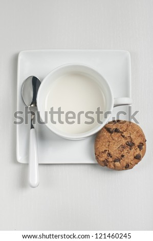 Closeup top view of cup with milk, spoon and chocolate cookie on plate on white wooden background. - stock photo