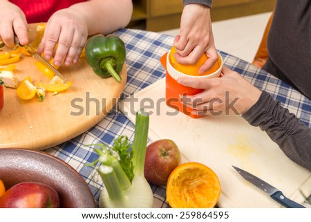 closeup two women cooking together in the kitchen - stock photo