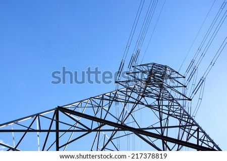 closeup underview of towering steel pylon supporting electric power cables - stock photo