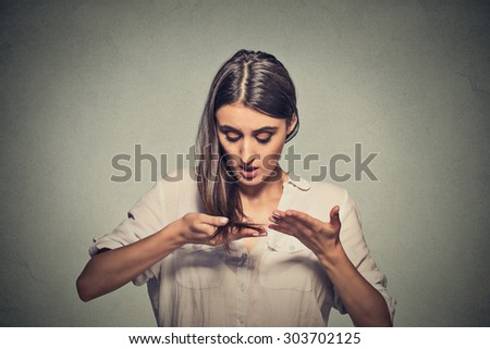 Closeup unhappy frustrated young woman surprised she is losing hair, receding hairline. Gray background. Human face expression emotion. Beauty hairstyle concept  - stock photo
