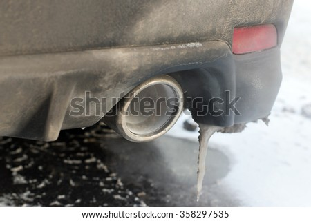 Closeup up of a car exhaust pipe with running engine, selective focus shot