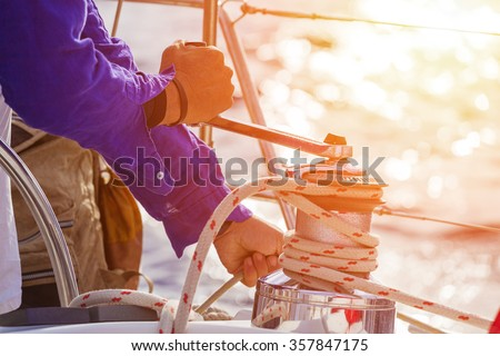 Closeup up of Yachtsman hands dealing with yacht ropes .Lens flare, unrecognizable person - stock photo