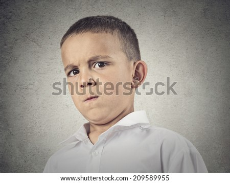 Closeup up portrait, headshot suspicious, cautions child, boy looking at you with disbelief, skepticism, isolated grey wall background. Human facial expressions, emotions, body language, perception - stock photo