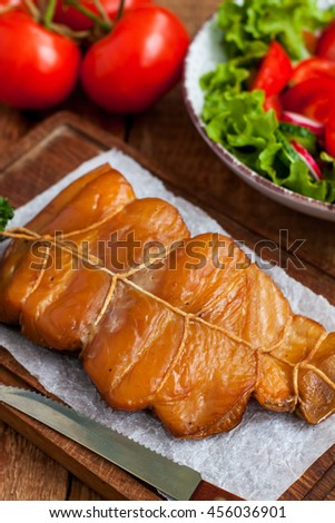 Closeup vertical view of smoked white fish fillet on wooden serving board with vegetales - stock photo