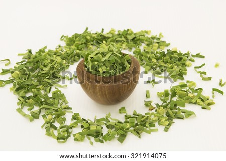 Closeup view focusing on pandan leaf or screw pine in a wooden bowl. The long green fresh leaf is finely shredded or chopped to make herbal tea of sweet fragrance that have medicinal benefits. - stock photo