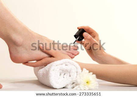 Closeup View Of A Beautician's Hand Applying Nail Varnish To Woman's Feet - stock photo