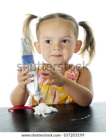 Closeup view of a beautiful preschooler looking pleased with her efforts to load her own toothbrush with toothpaste.  On a white background. - stock photo
