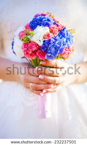 Closeup view of a bride holding bouquet of flowers - stock photo