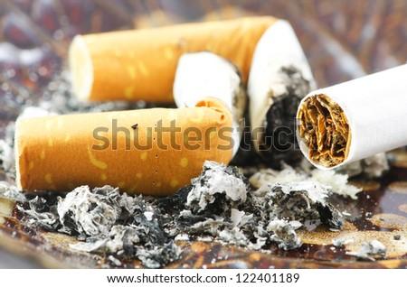 Closeup view of a cigarette and ashtray - stock photo