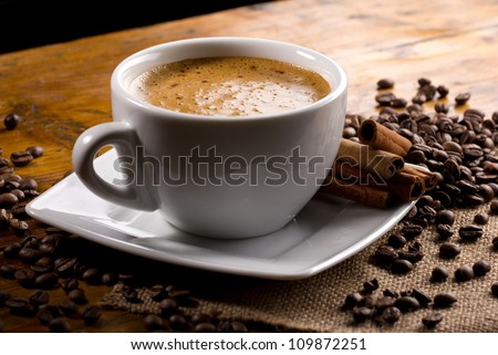closeup view of a cup of coffee with cinnamon sticks and coffee beans - stock photo
