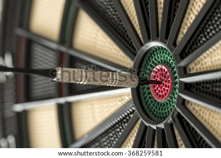 Closeup view of a dart in the red center of a target. - stock photo