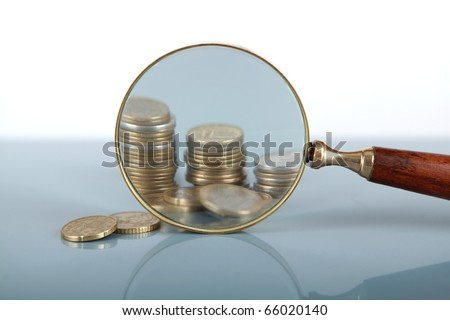 Closeup view of a magnifying glass looking at a stack of coins