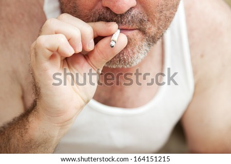 Closeup view of a man smoking a marijuana joint.  **Dramatization - no illegal narcotics were used in the making of this photograph** - stock photo