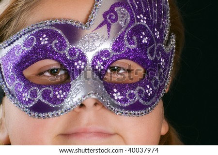 Closeup view of a masked girl shot on black