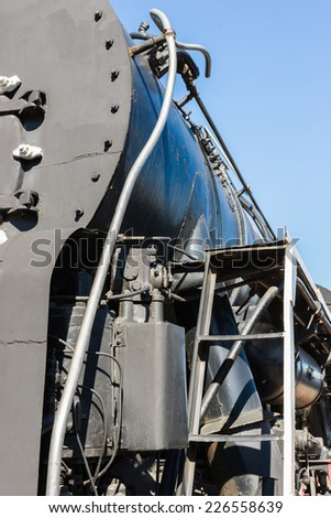 Closeup view of a mechanical equipment around a steam locomotive boiler. Frames, tubes, and cylinders of black color against the background of blue sky. Vertical, portrait orientation photography - stock photo