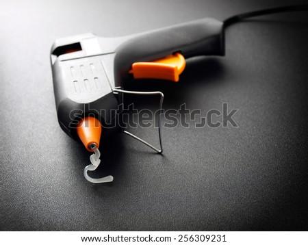 Closeup view of a modern electric glue gun. - stock photo