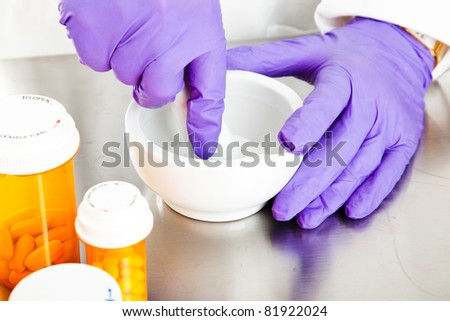 Closeup view of a pharmacist's hands, using a mortar and pestle. - stock photo