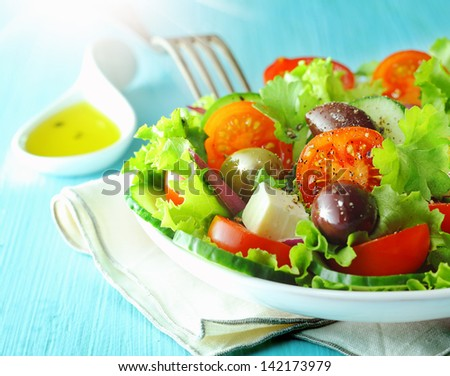 Closeup view of a plate of healthy fresh Greek feta and olive salad with crisp lettuce and tomato for a delicious Mediterranean cuisine - stock photo