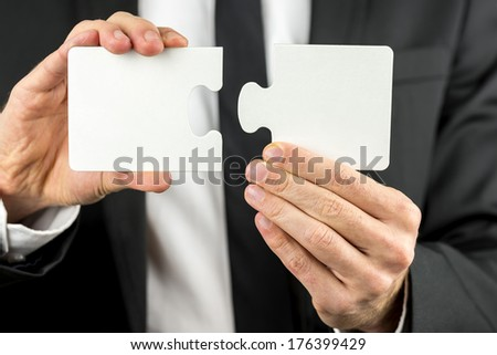 Closeup view of a professional businessman in a suit holding two pieces of a blank puzzle in his hand ready to fit them together in a concept of problems, planning, cooperation and solutions. - stock photo