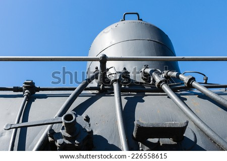 Closeup view of a sand dome on top of steam locomotive boiler against the background of clear blue sky - stock photo