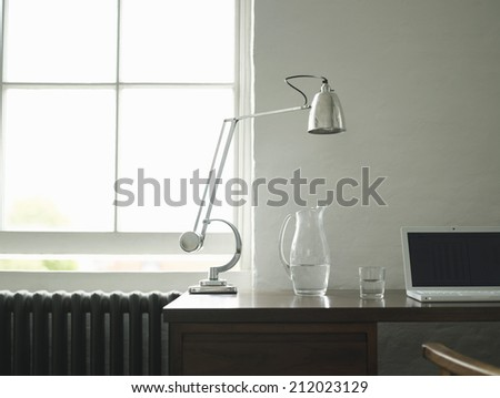 Closeup view of a study desk with laptop and lamp - stock photo