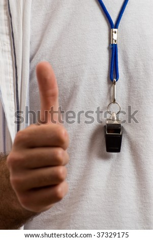 Closeup view of a thumbs up and a blow whistle around someone's neck - stock photo