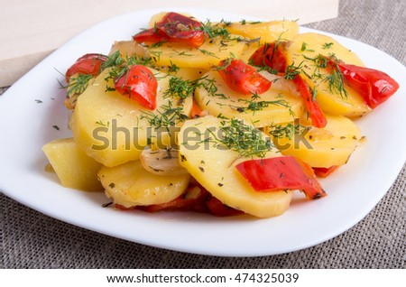 Closeup view of a vegetarian dish of organic ingredients - slices of stewed potatoes and peppers on sackcloth background