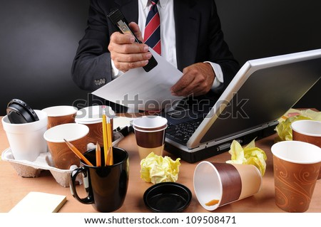 Closeup view of a very cluttered and stressed out business mans desk. Man is stapling papers with coffee cups and crumpled papers litter his workspace. Horizontal on a light to dark gray background. - stock photo
